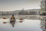 Woman paddling a kayak on Tully Lake in Royalston, MA on a very calm morning
