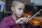 Young boy playing a violin at his music lesson in school