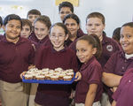 School kids with a tray of cupcakes