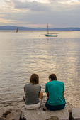 A couple sit on the edge of Lake Champlain in Vermont at sunset