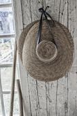 A woman's bonnet hanging on a hook in a farmhouse