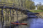 A kayaker travels under the Old North Bridge on the Concord River in Concord, MA