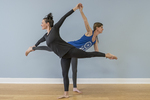 Two women in a yoga class doing poses