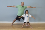 A dad and his daughter in a yoga class