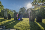 Sunlight shining over the gravestones at an old cemetery in Petersham, MA