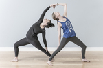 Two women doing a yoga pose in the studio