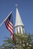 A flag flies next to the steeple of the Trinitarian Congregational Church in Concord, MA