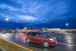 A red van drives through a parking lot in Hadley, MA just after a thunderstorm