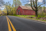 Old red barn in Petersham, MA on the edge of the road with a yellow line