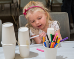 Little girl drawing a design on a cup