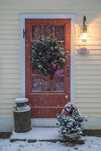 Christmas wreath on a red door and snow
