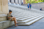 Woman sitting on the steps of the Harvard Library reading