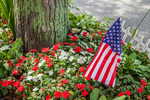 American flag in a flower bed along the sidewalk in Rockport, MA