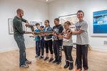 Children holding and learning about a boa constrictor at an animal show