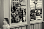 Woman photographed through a window looking at her smartphone - Harvard Square