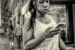 Young woman looking at her smartphone as she walks along Mass Ave in Cambridge, MA