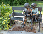 A sculpture of two children sitting on a bench reading at a rural New England  library