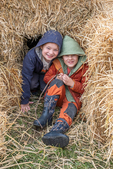 Two kids playing in straw bales.