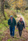 An older couple walking along a dirt road in the autumn