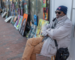 An artist sits with his paintings on the street in Harvard Square, Cambridge, MA