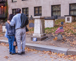 A couple looking at Paul Revere's grave in The Old Granary Burying Ground on Tremont Street in Boston, MA