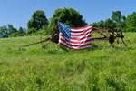 American flag hung on farm machinery in a field