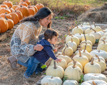 Mom and her young son picking out a pumpkin at a farm