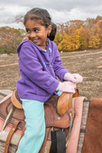 Young girl happily riding on a horse at a fair
