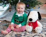 A little boy and his stuffed animal friend sitting under the Christmas tree