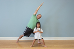 A dad and his daughter doing yoga together