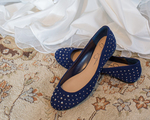 A bride's wedding dress and a pair of blue shoes for the bride to wear at her wedding