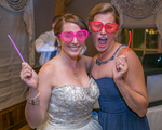 A bride and her bridesmaid enjoying the wedding day reception