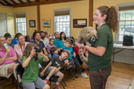 A woman educating a group of children and adults about wild animals at Fruitlands Museum in Harvard, MA