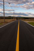 A yellow line in a newly paved road late in the afternoon in Templeton, MA, Mt Monadnock in the far distance