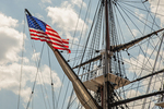 An American flag flies from the bow of the Costitution in the Charlestown Navy yard