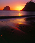 LF 253.  A starburst is created as the sun sinks over the edge of Cape Kiwanda with Haystack Rock on its shoulder.  Central Oregon Coast.