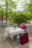 D3X 232 PI.  A tourist relaxes in the park like setting of the outside dining area of a rural restaurant in Tuscany, Italy