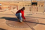 A visitor in four states at once at Four Corners, the point where state lines all meet.  (model released)