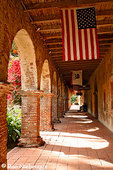 Flowers and the North Corridor at the Historic Mission San Juan Capistrano, Orange County, California.