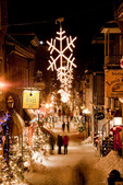 Snowflake lights hang over Rue du Petit-Champlain and the shoppers and tourists wandering in the Quartier Petit Champlain - the heart of New France, decorated festively for the Christmas holidays in the historic old City of Quebec, Quebec