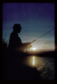 Angler fishing from shore at sunset.