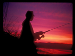 Silhouette of a Fisherman on the shore of a lake against a colorful Sunset.