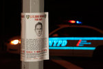 Poster of crime suspect and NYPD car at night