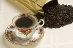 bone china cup and saucer with coffee and coffee beans spilling out of gold bag